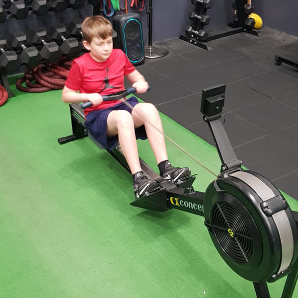 boy on rower in private gym with comotion fitness trainer colleen madden